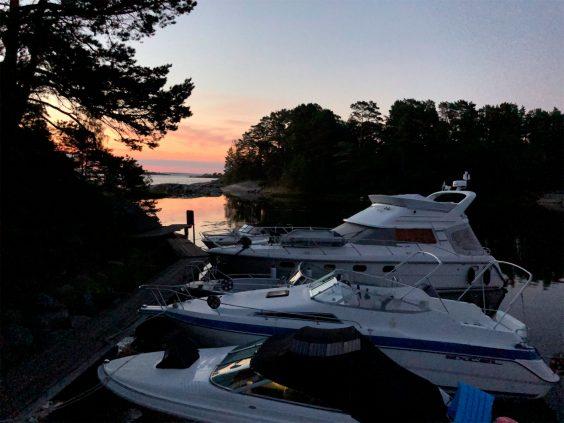 Skymning på skärgårdsö, blankt vatten, fyra motorbåtar i olika storlek ligger förtöjda.